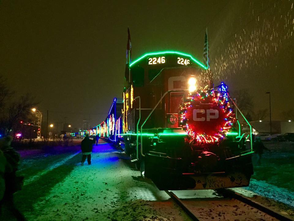 Canadian Pacific Holiday Train arrives on a snowy night, decorated in thousands of colored lights.