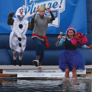People dressed in Frozen costumes leap from a platform into a frozen lake as part of the Fire and Ice Plunge charity event.