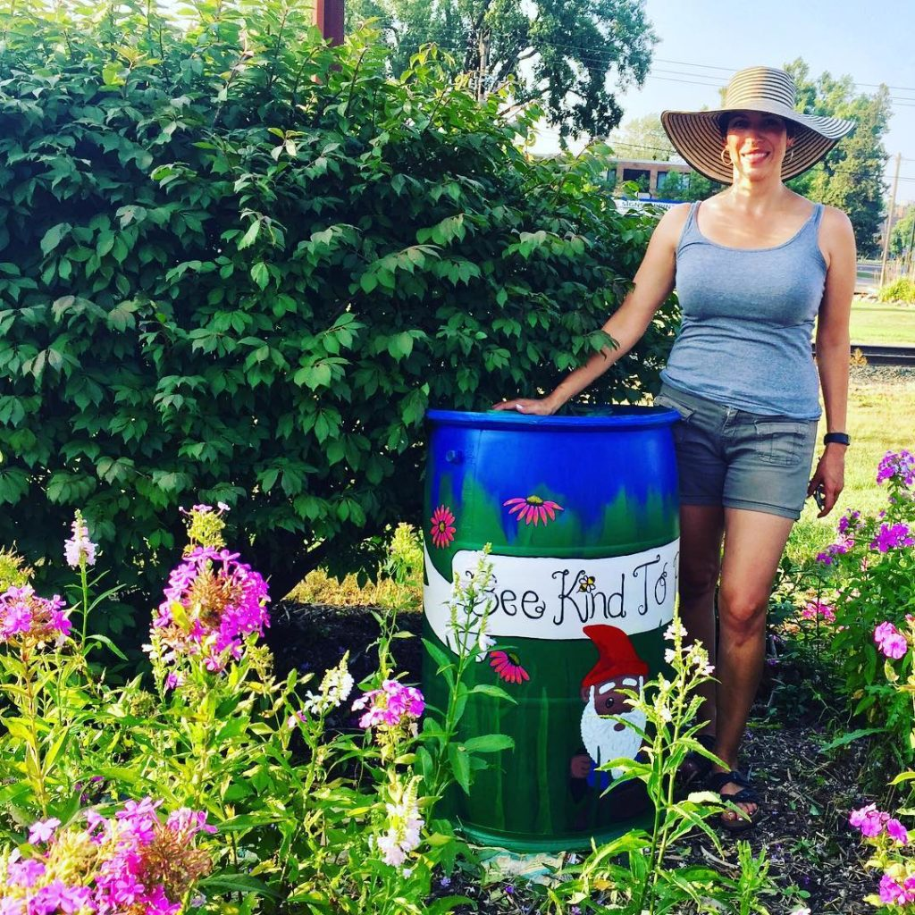 A gardener stands by a rain barrel painted with pollinators and garden gnomes.