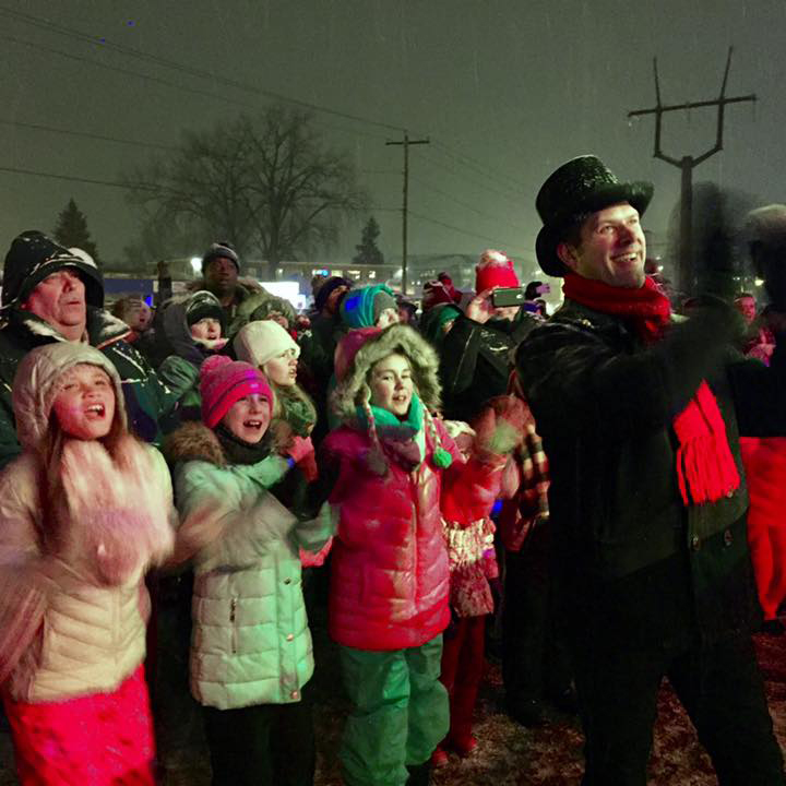 Carolers in bright outfits and cheerful hats sing along with the band aboard the Canadian Pacific Holiday Train.