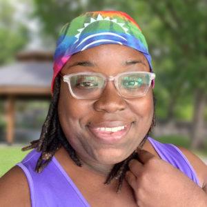 A black woman wearing a tie-dye HeightsNEXT bandana.