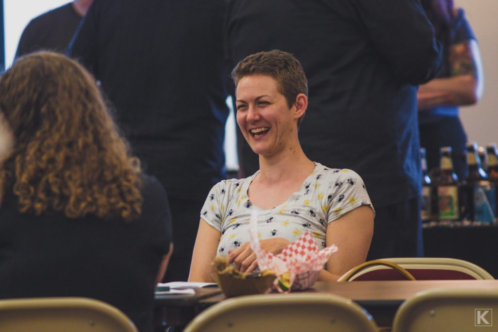 A laughing woman at a beer tasting event.