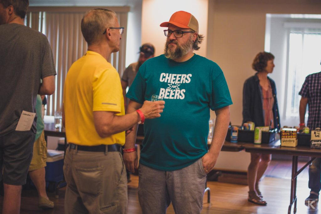 Two people talking at a beer tasting event.