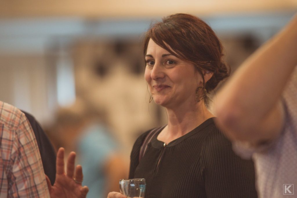 A smiling woman at a beer tasting event.