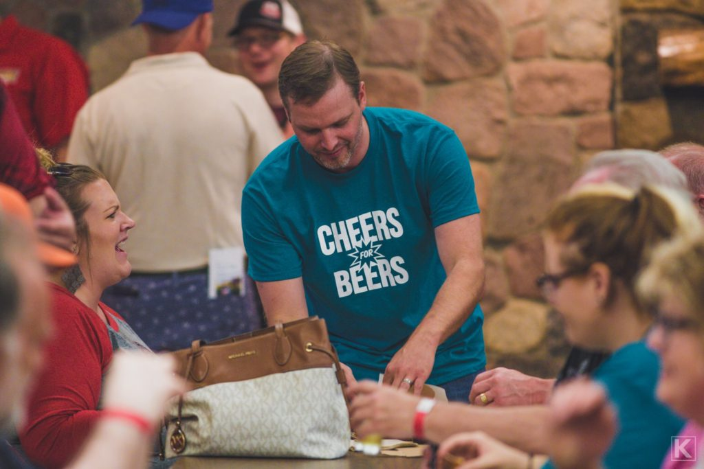 A volunteer helps bus tables at a beer tasting event.