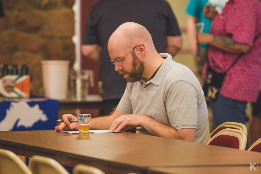 A beer critic takes notes at a beer tasting event.