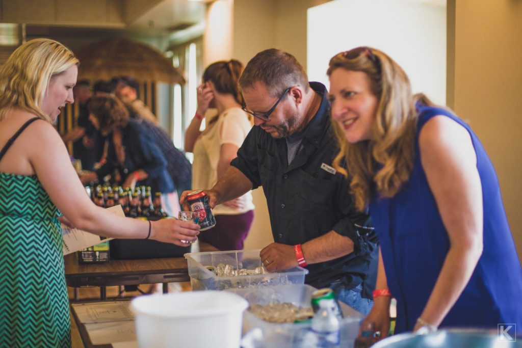Brewers pouring beer samples for people.
