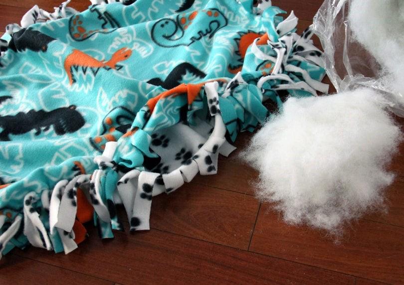 Adding fiber fill stuffing through an opening in the fleece fringe strips.