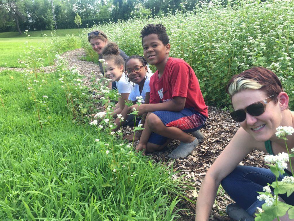 Diverse volunteers and kids work in a garden.