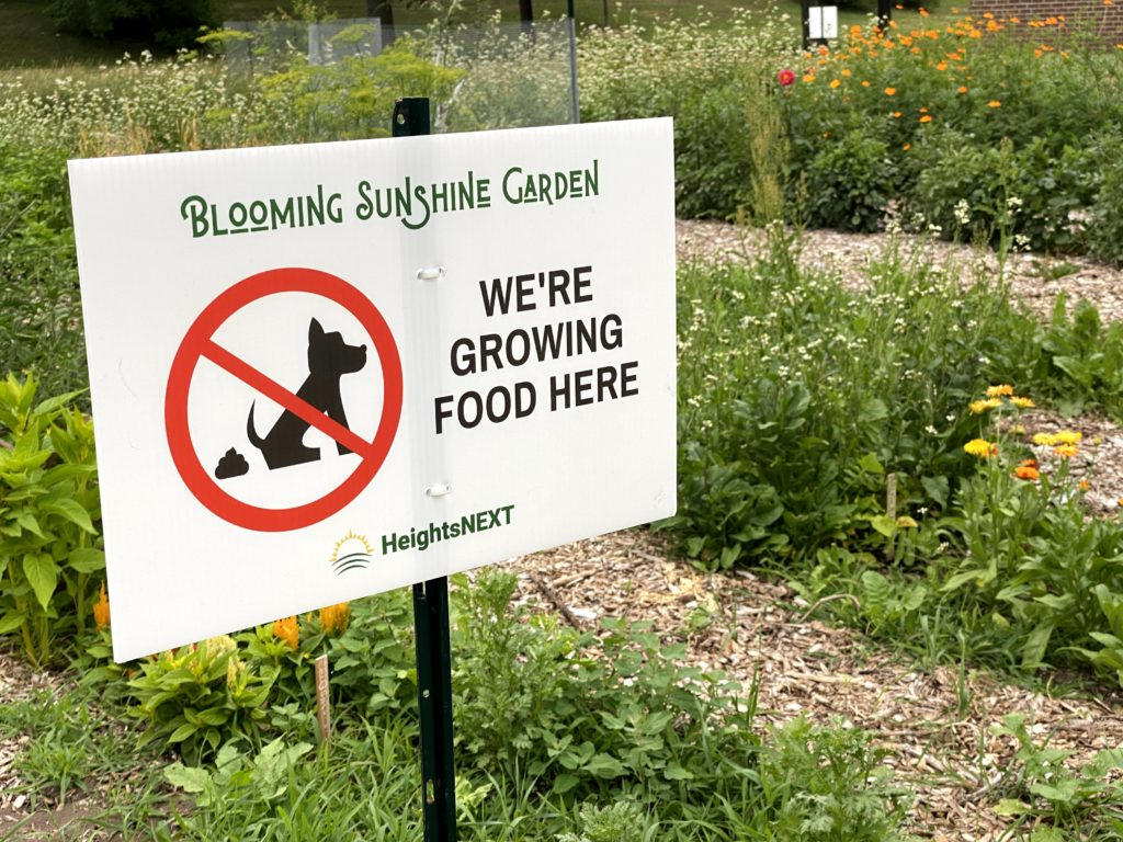 """A Blooming Sunshine Garden sign prohibiting dog poop reads """"We're growing food here."""""""