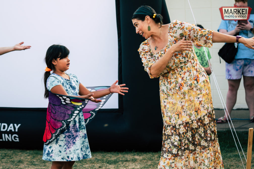 A girl in a butterfly costume dances with Mayor Amáda Márquez Simula at the 2021 Monarch Festival in Columbia Heights, MN