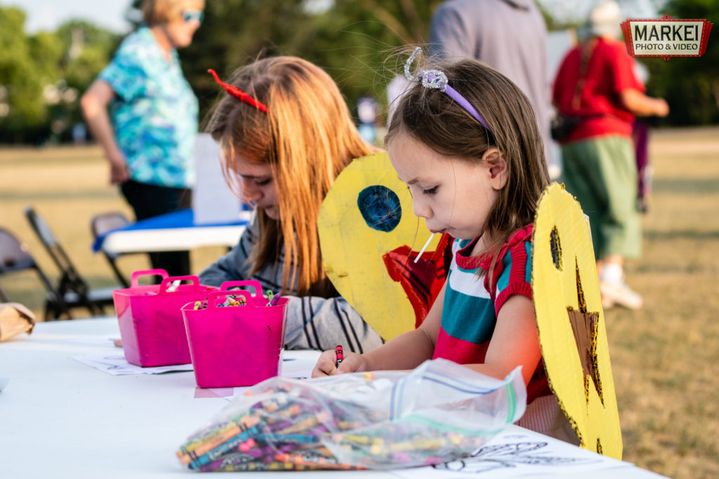 Kids in butterfly costumes do a coloring activity at the 2021 Monarch Festival in Columbia Heights, MN