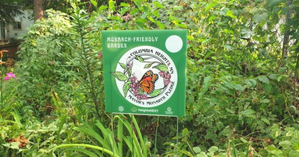 Mayor's Monarch Pledge lawn sign in a pollinator friendly garden